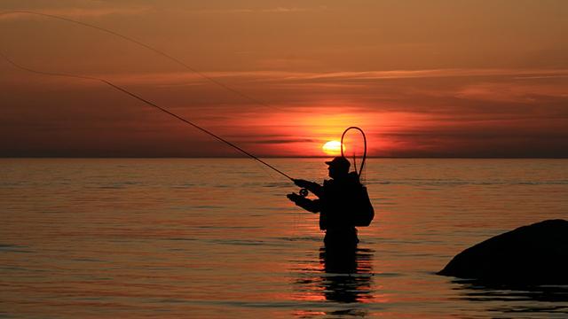 夕暮れでウエーディングする釣り好きルアーマン