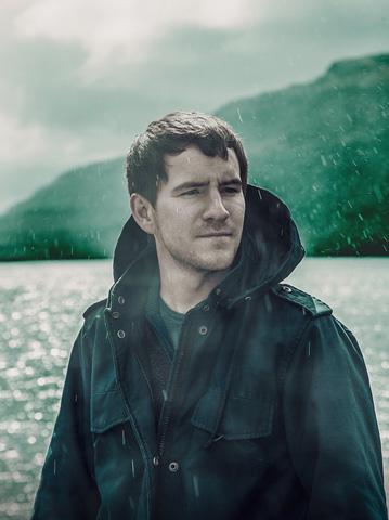 レインウエアを着て雨の中たたずむ男性画像